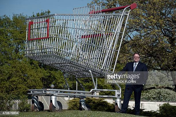 New President and CEO of Caddie a French manufacturer of supermarket trolleys Stephane Dedieu poses beside a giant trolley on April 20 2015 at the...