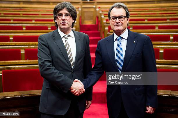 New President of Catalonia Carles Puigdemont shakes hands with former President of Catalonia Artur Mas after being elected as the new President of...