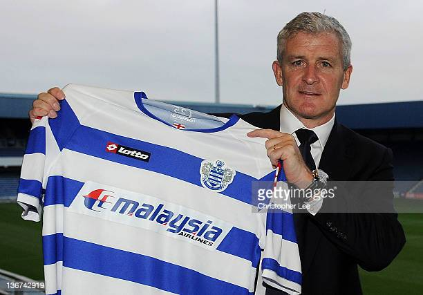 New Queens Park Rangers manager Mark Hughes holds up a QPR shirt during the unveiling of the new Queens Park Rangers Manager at Loftus Road on...