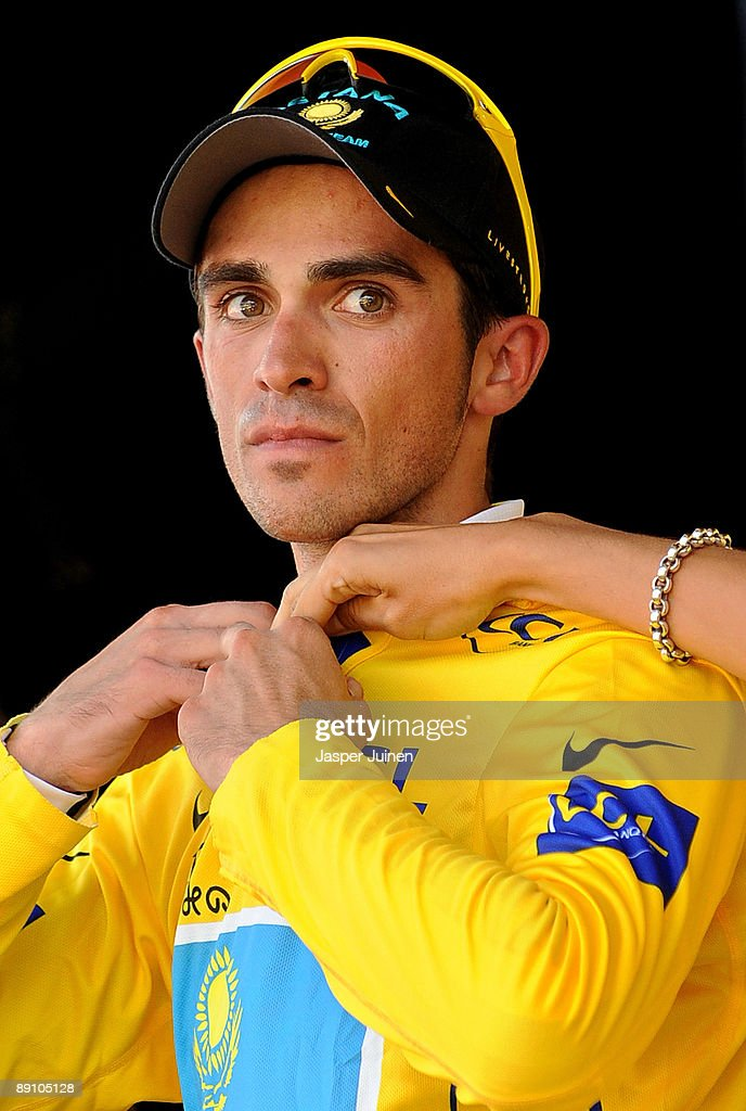 New race leader Alberto Contador of Spain and team Astana receives a hand adjusting the yellow jersey on the podium after he won stage 15 of the 2009 Tour de France from Pontarlier to Verbier on July 19, 2009 in Verbier, Switzerland.