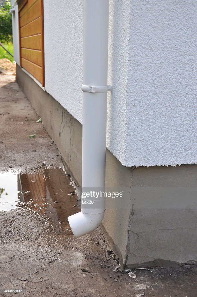 New rain gutter and downspouts on house construction with puddle. : Stock Photo