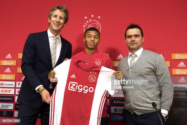 New recruit Brazilian forward David Neres Campos poses with Ajax Amsterdam football club's marketing directors Edwin van der Sar and Marc Overmars...