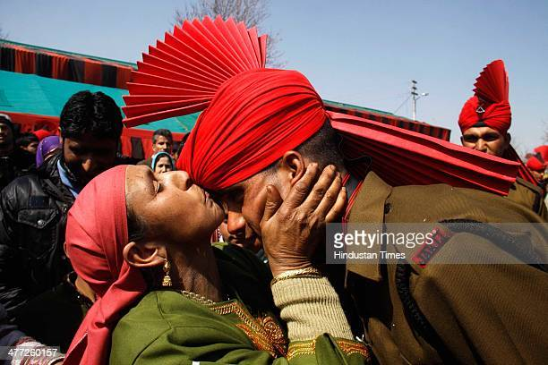 New recruit of the Jammu Kashmir Light Infantry Regiment kissed by his mother during a passing out parade at an army base on March 8 2014 in Srinagar...