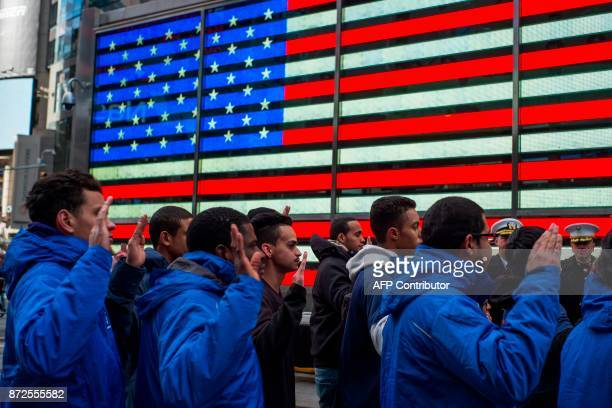 New recruits raise their hands as they take an oath outside the renovated Times Square Military Recruiting Station in New York on November 10 2017...