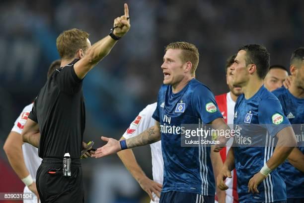 New referee Soeren Storks argues with Andre Hahn of Hamburg and Filip Kostic of Hamburg the Bundesliga match between 1 FC Koeln and Hamburger SV at...