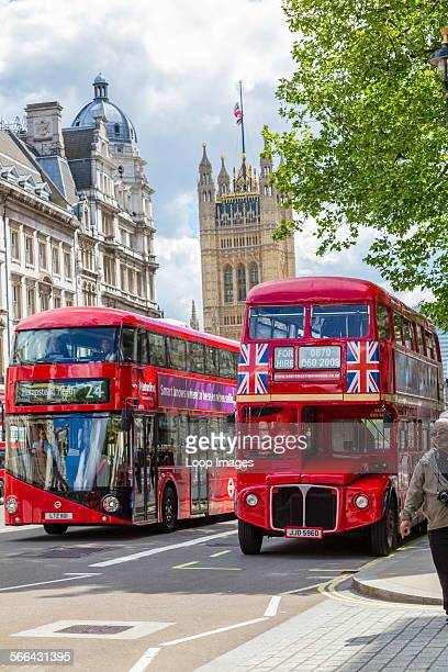 A new Routemaster bus passes an original bus in front of the Houses of Parliament