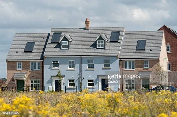 New row of houses in England viewed over meadow