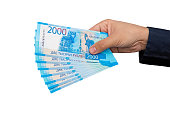 new Russian banknotes denominated in 2000 rubles in male hands close-up isolated on white background. 18000 rubles with new two thousand dollar bills
