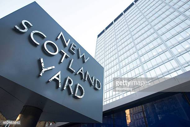 A 'New Scotland Yard' logo sits on a revolving sign outside the headquarters of London's Metropolitan Police Service in London UK on Monday Dec 15...