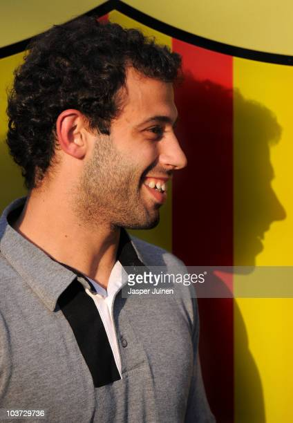 New signing Javier Mascherano smiles as he cast his shadow in the background during his presentation as new Barcelona player at the Camp Nou stadium...