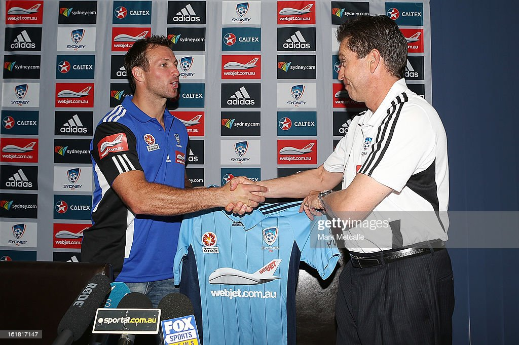 New signing Lucas Neill is presented with a Sydney FC jersey by Coach Frank Farina during a Sydney FC press conference at Macquarie Uni on February 17, 2013 in Sydney, Australia.