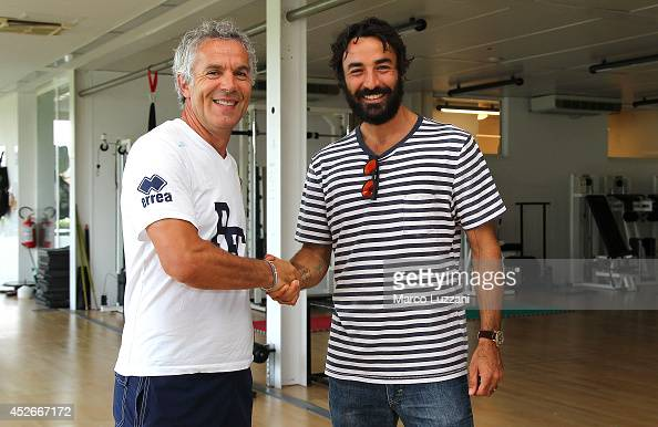 New signing Mattia Cassani shakes hands with Parma FC coach Roberto Donadoni before FC Parma Training Session at the club's training ground on July...
