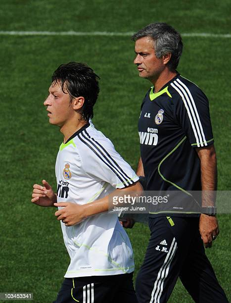 New signing Mesut Ozil of Real Madrid runs past his coach Jose Mourinho during a training session at the Valdebebas training ground on August 19 2010...