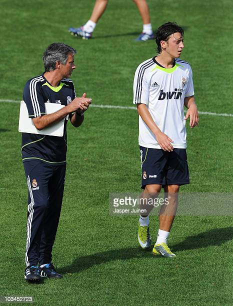New signing Mesut Ozil of Real Madrid watches on besides his coach Jose Mourinho during a training session at the Valdebebas training ground on...