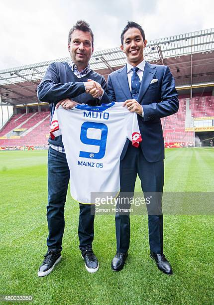 New signing player Yoshinori Muto of 1 FSV Mainz 05 shakes hands with manager Christian Heidel during his unveiling at Coface Arena during on July 9...