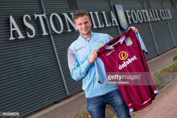 New signing Tom Cleverley of Aston Villa poses with a match shirt at the club's training ground at Bodymoor Heath on September 03 2014 in Birmingham...