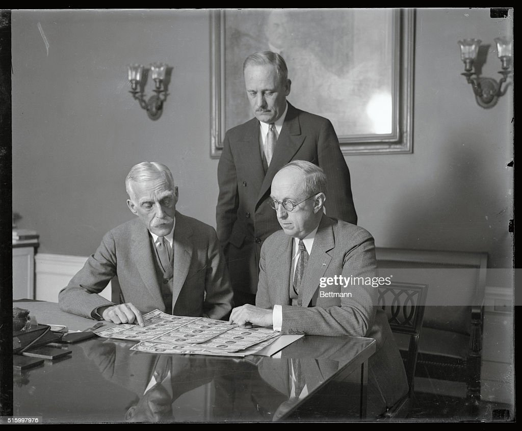 New small-size currency to be issued July 10th...Secretary of the Treasury <a gi-track='captionPersonalityLinkClicked' href=/galleries/search?phrase=Andrew+Mellon&family=editorial&specificpeople=908430 ng-click='$event.stopPropagation()'>Andrew Mellon</a> pictured with Assistant Secretary Henry Herrick Bond (seated) are shown the new bills by Director Hall of the Bureau of Engraving and Printing, Washington, D.C. The new small-size currency will be issued July 10th.