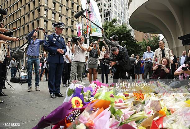 New South Wales Police Commissioner Andrew Scipione stands in front of flowers left as a sign of respect at Martin Place on December 16 2014 in...