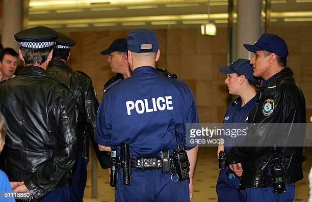 New South Wales police confer after the arrival back of United Airlines Los Angelesbound flight UA840 at Sydney International Airport 27 July 2004 A...