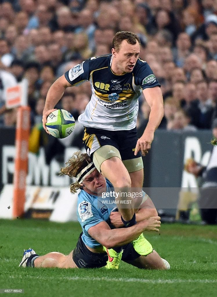 New South Wales Waratah's flanker Michael Hooper (L) tackles ACT Brumbies fullback Jesse Mogg (R) in their Super 15 semi-final rugby match in Sydney on July 26, 2014. AFP PHOTO/William WEST --IMAGE