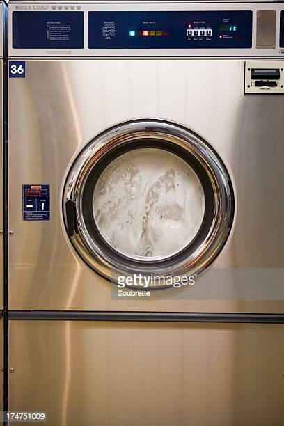 New stainless steel washing machine running at a laundromat