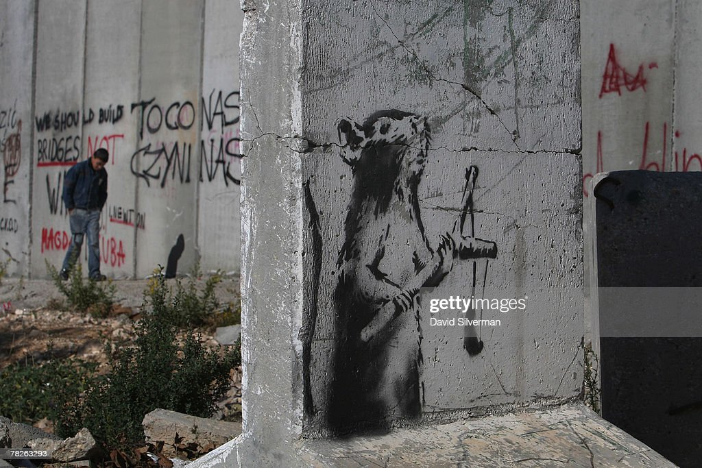 A new stencil painting on a concrete barricade by elusive British graffiti artist Banksy shows a rat holding a slingshot December 5, 2007 opposite an Israeli army guard post (unseen) where Israel's separation barrier cuts into the biblical city of Bethlehem in the West Bank. The Bristol-born artist has adorned Israel's West Bank separation barrier and Bethlehem walls with new images, including one of a dove wearing a flak jacket and a soldier being frisked by a young girl. His works, along with those of other international artists, are part of an exhibition called Santa's Ghetto.