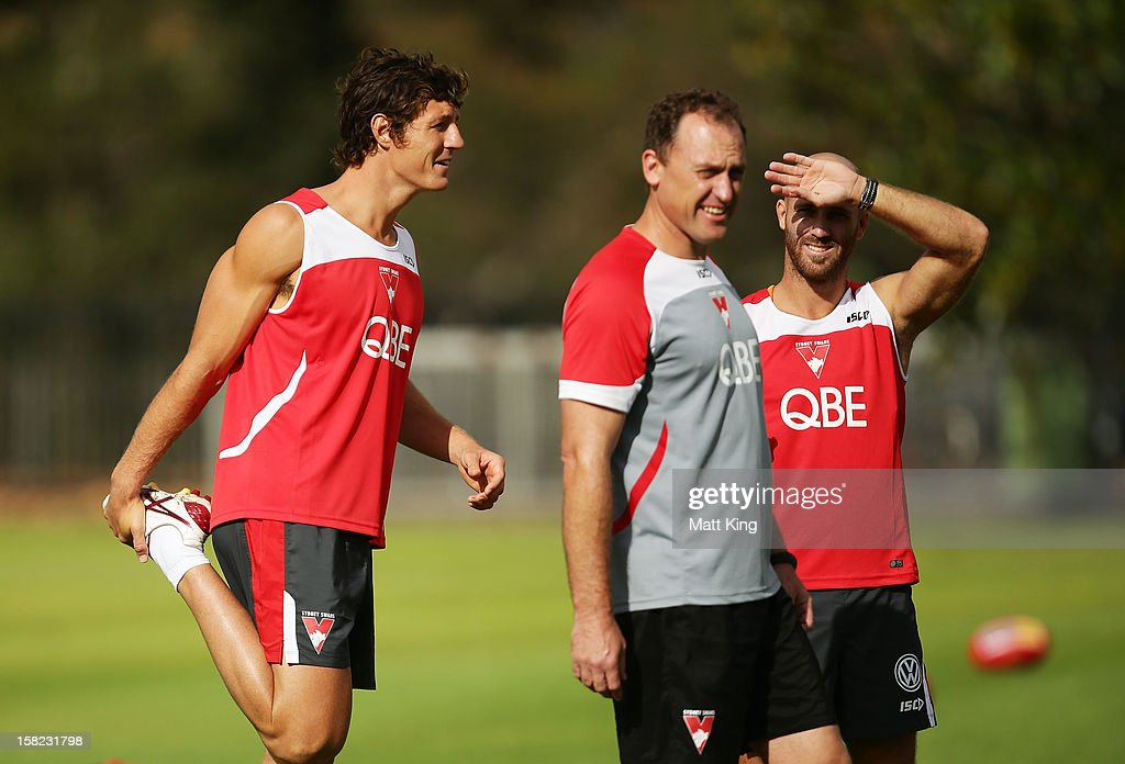 New Swans signing Kurt Tippett (L) stretches behind Swans coach John Longmire (C) and <a gi-track='captionPersonalityLinkClicked' href=/galleries/search?phrase=Jarrad+McVeigh&family=editorial&specificpeople=3083250 ng-click='$event.stopPropagation()'>Jarrad McVeigh</a> (R) during a Sydney Swans AFL training session at Moore Park on December 12, 2012 in Sydney, Australia.