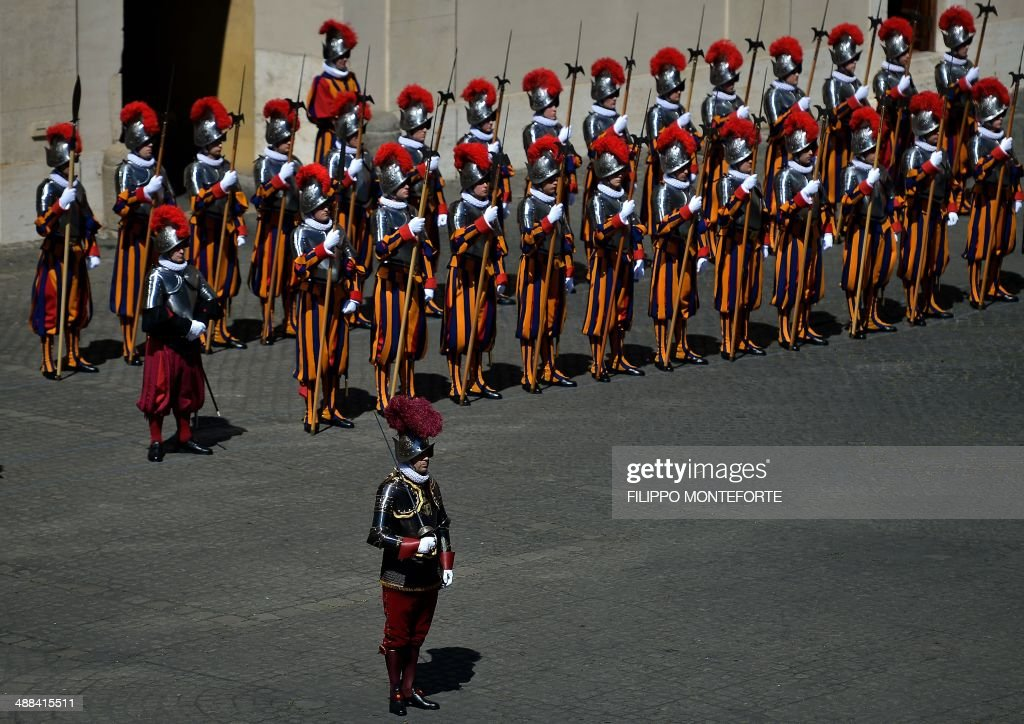 New Swiss Guard recruits stand to attend a swearing in ceremony in San Damaso square at the Vatican on May 6, 2014. 35 new recruits sworn-in on the anniversary of the sack of Rome when they protected Pope Clement VII hideout at castel Sant' Angelo on May 6, 1527. AFP PHOTO/ Filippo MONTEFORTE