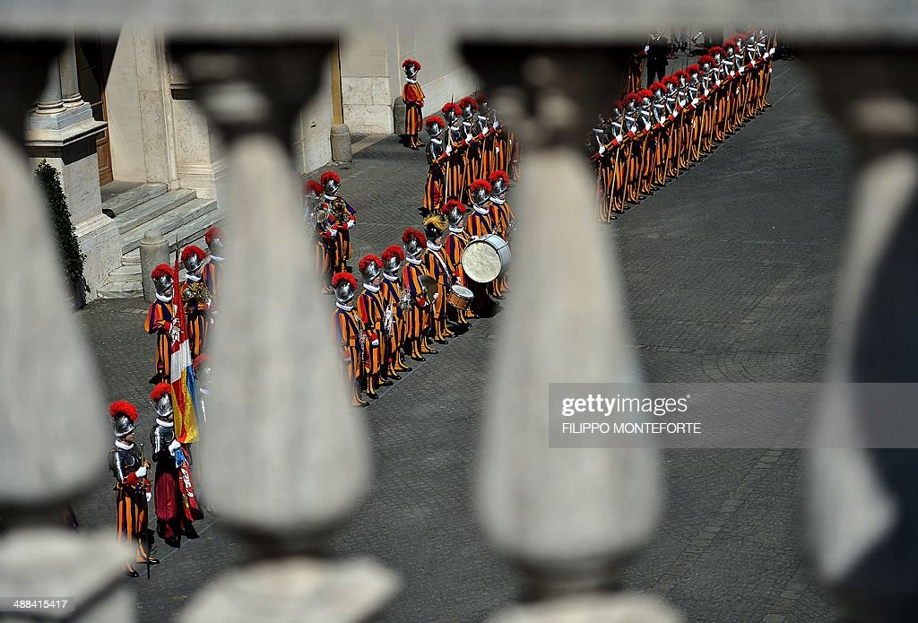New Swiss Guard recruits stand to attend a swearing-in ceremony in San Damaso square at the Vatican on May 6, 2014. 35 new recruits sworn-in on the anniversary of the sack of Rome when they protected Pope Clement VII hideout at castel Sant' Angelo on May 6, 1527. AFP PHOTO/ Filippo MONTEFORTE