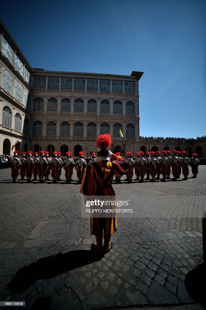 New Swiss Guards recruit stand after swearing-in during a ceremony in San Damaso square at the Vatican on May 6, 2014. 35 new recruits sworn-in on the anniversary of the sack of Rome when they protected Pope Clement VII hideout at castel Sant' Angelo on May 6, 1527. AFP PHOTO/ Filippo MONTEFORTE