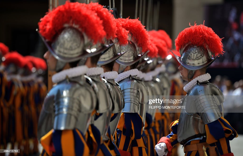 A new Swiss Guards recruit swear in during a ceremony in San Damaso square at the Vatican on May 6, 2014. 35 new recruits sworn-in on the anniversary of the sack of Rome when they protected Pope Clement VII hideout at castel Sant' Angelo on May 6, 1527. AFP PHOTO/ Filippo MONTEFORTE