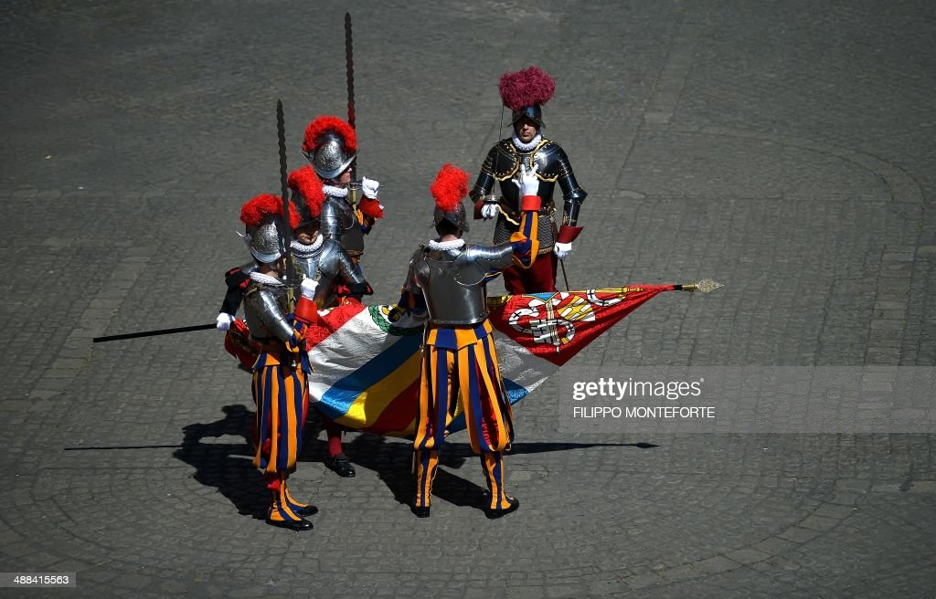 A new Swiss Guards recruit swear-in during a ceremony in San Damaso square at the Vatican on May 6, 2014. 35 new recruits sworn-in on the anniversary of the sack of Rome when they protected Pope Clement VII hideout at castel Sant' Angelo on May 6, 1527. AFP PHOTO/ Filippo MONTEFORTE