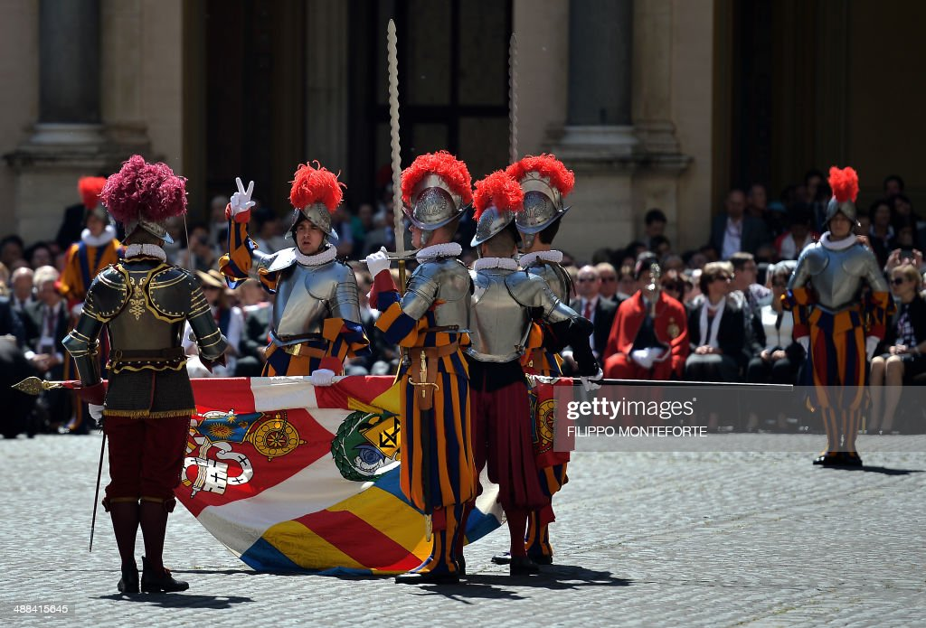 A new Swiss Guards recruit swears-in during a ceremony in San Damaso square at the Vatican on May 6, 2014. 35 new recruits sworn-in on the anniversary of the sack of Rome when they protected Pope Clement VII hideout at castel Sant' Angelo on May 6, 1527. AFP PHOTO/ Filippo MONTEFORTE