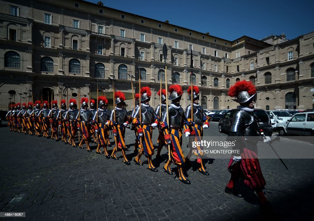 New Swiss Guards recruit walk back after swearing-in during a ceremony in San Damaso square at the Vatican on May 6, 2014. 35 new recruits sworn-in on the anniversary of the sack of Rome when they protected Pope Clement VII hideout at castel Sant' Angelo on May 6, 1527. AFP PHOTO/ Filippo MONTEFORTE