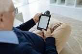 Senior man sitting on sofa and using e-reader