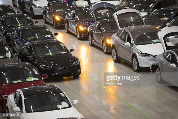 A new Tesla Model X sports utility vehicle second right sits with Tesla Model S automobiles following assembly for the European market at the Tesla...