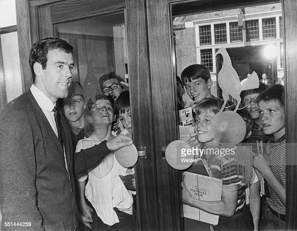 New Tottenham Hotspur football player Mike England greeting a group of young fans behind glass doors at White Hart Lane London August 19th 1966