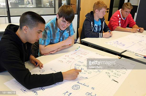 New trainees write their names and draw pictures of their interests on their first day at a Siemens training center on September 3 2012 in Berlin...