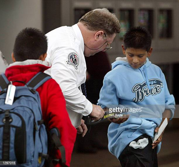 A new Transportation Security Agency employee checks a young traveler's pocket contents as he passes through a security checkpoint in Terminal...