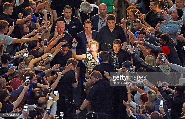 New UFC women's bantamweight champion Holly Holm of the United States celebrates as she makes her way through the crowd as she leaves the arena after...