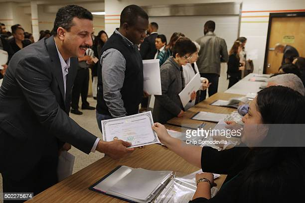 New United States citizens line up to receive their certificates of citizenship following their naturalization ceremony at Oakton High School...