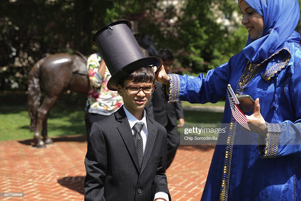 New U.S. citizen Yahya Ahmed Aflal, 6, originally from Morocco, gets a little help from his mother with his hand-made paper stovepipe hat, following a childrens citizenship ceremony at President Lincoln's Cottage at the Soldiers' Home May 2, 2016 in Washington, DC. Twenty one children from 19 countries, including Syria, South Korea and El Salvador, became new United States citizens during the ceremony sponsored by the U.S. Citizenship and Immigration Services. President Abraham Lincoln and his family resided seasonally on the grounds of the Soldiers' Home to escape the heat and politics of downtown Washington, as did President James Buchanan before him and presidents Rutherford B. Hayes and Chester A. Arthur from 1885 to 1887.