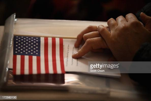 A new US citizens holds and American flag along with her citizenship papers as she participates in a naturalization ceremony at the Chicago Cultural...