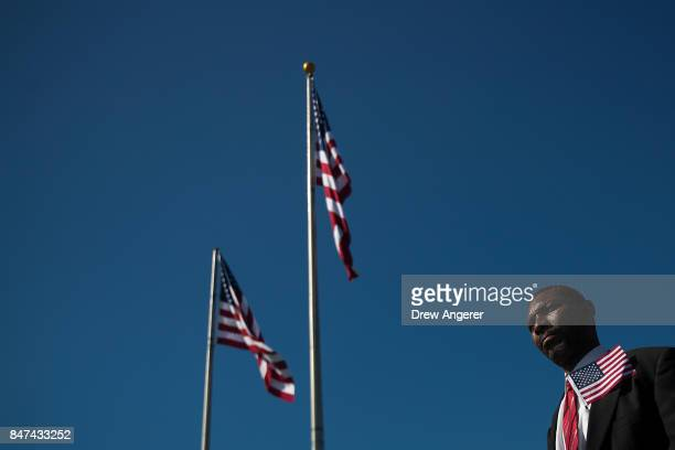 New US citizens stand for the signing of 'America the Beautiful' at the conclusion of a naturalization ceremony at Liberty State Park September 15...