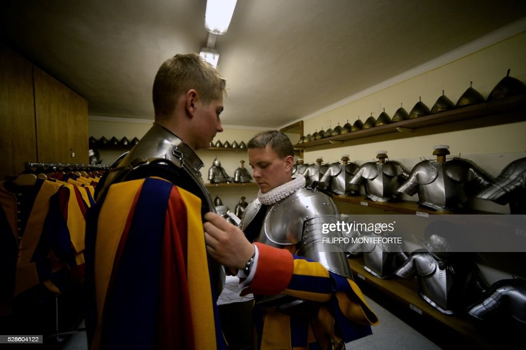 New Vatican Swiss Guards adjust their uniforms prior to a swearing-in ceremony in Vatican City, on May 6, 2016. The annual swearing in ceremony for the new papal Swiss guards takes place on May 6, commemorating the 147 who died defending Pope Clement VII on the same day in 1527. / AFP / FILIPPO