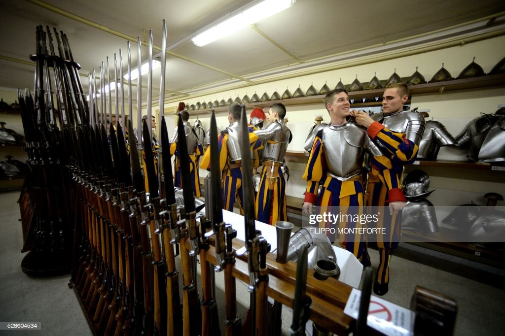 New Vatican Swiss Guards help each other as they adjust their uniforms prior to a swearing-in ceremony in Vatican City, on May 6, 2016. The annual swearing in ceremony for the new papal Swiss guards takes place on May 6, commemorating the 147 who died defending Pope Clement VII on the same day in 1527. / AFP / FILIPPO