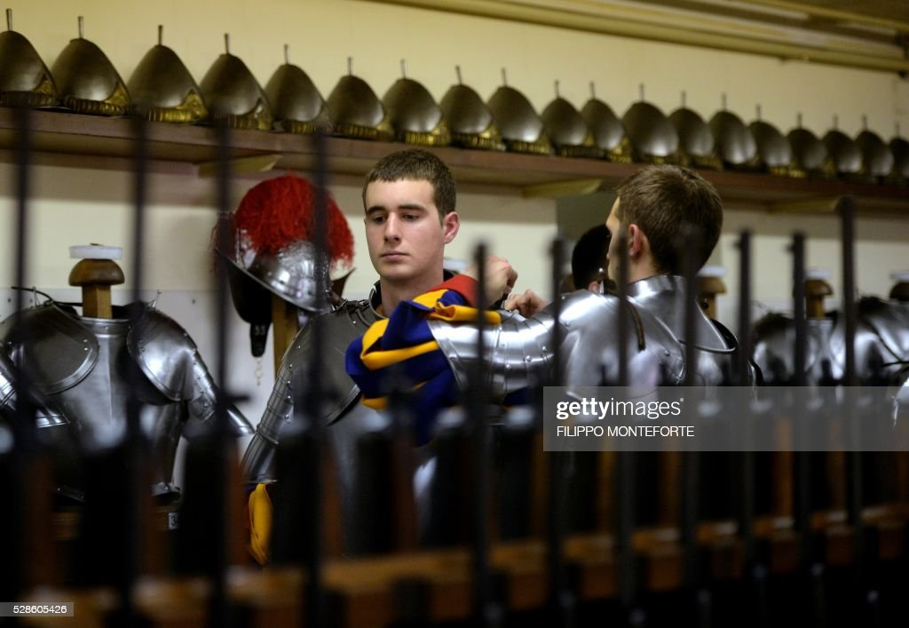 New Vatican Swiss Guards put on and adjust their uniforms prior to a swearing-in ceremony in Vatican City, on May 6, 2016. The annual swearing in ceremony for the new papal Swiss guards takes place on May 6, commemorating the 147 who died defending Pope Clement VII on the same day in 1527. / AFP / FILIPPO