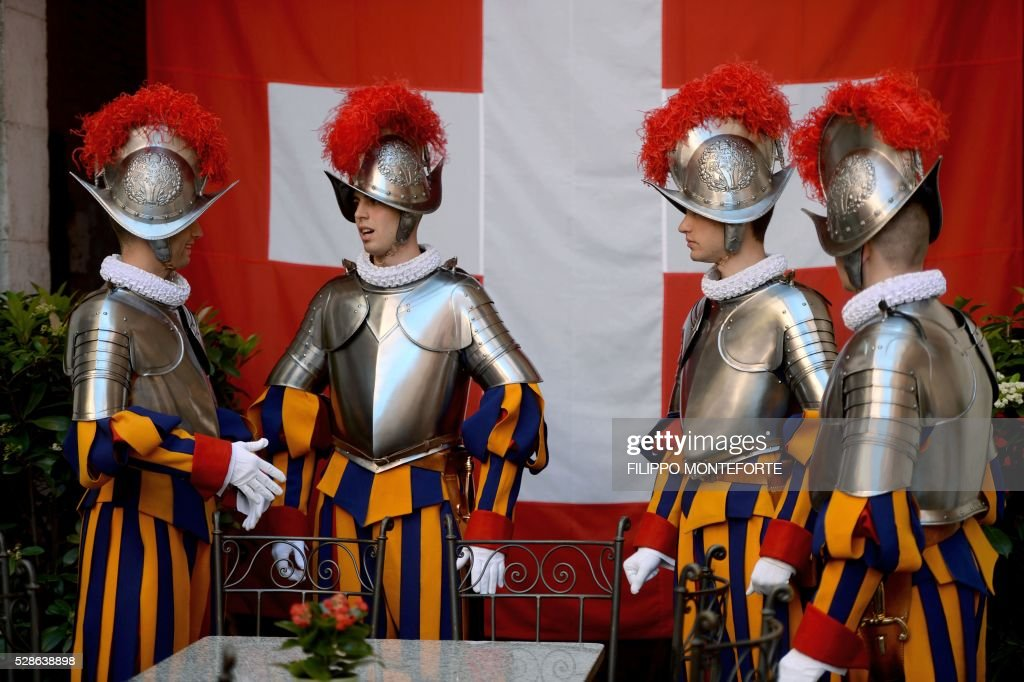 New Vatican Swiss Guards wearing their new uniforms, chat as they stand in front of their national flag prior to a swearing-in ceremony in Vatican City, on May 6, 2016. The annual swearing in ceremony for the new papal Swiss guards takes place on May 6, commemorating the 147 who died defending Pope Clement VII on the same day in 1527. / AFP / FILIPPO