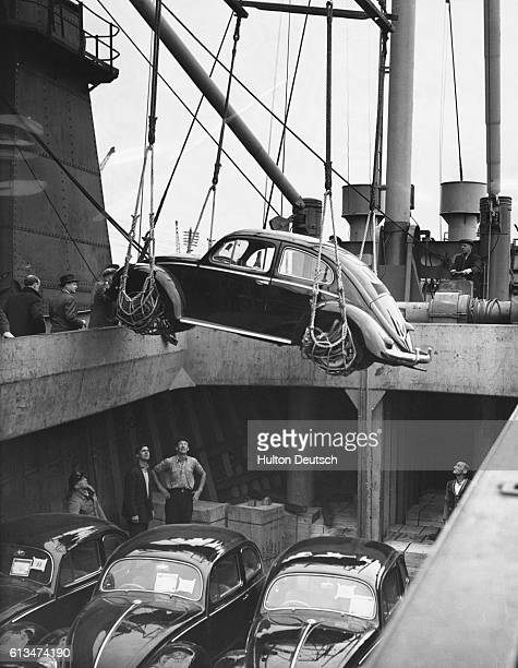 New Volkswagen Beetles arrive for import into Britain for the first time They are lifted from the ship the S S Titania onto the land at Surrey Docks