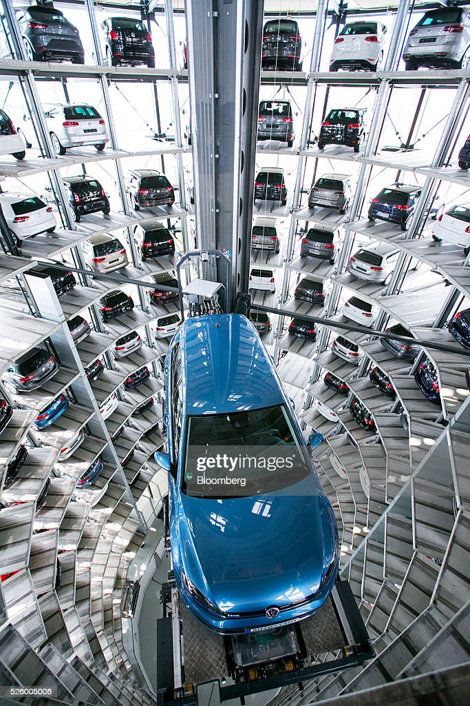 A new Volkswagen e-Golf electric automobile, produced by Volkswagen AG (VW), is transported on an elevation platform as new VW automobiles sit in storage bays inside one of the automaker's glass delivery towers at the VW factory in Wolfsburg, Germany, on Friday, April 29, 2016. Porsche Automobil Holding SE, the investment vehicle of the billionaire family that controls VW, stuck to a goal of making acquisitions beyond the beleaguered carmaker, even as its dwindling cash on hand reduces the scope of possible transactions. Photographer: Krisztian Bocsi/Bloomberg via Getty Images